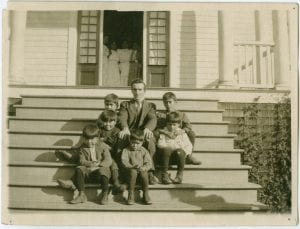 The preacher and the W.M.S. Home boys on the steps of the Home, Kitamaat