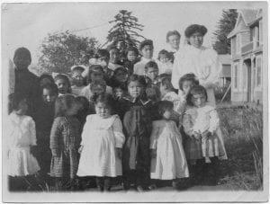 Some village children: Miss Kilbourne (nurse) in background