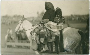Mother and children travelling on horseback