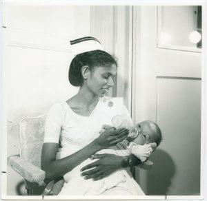 Nurse feeding infant